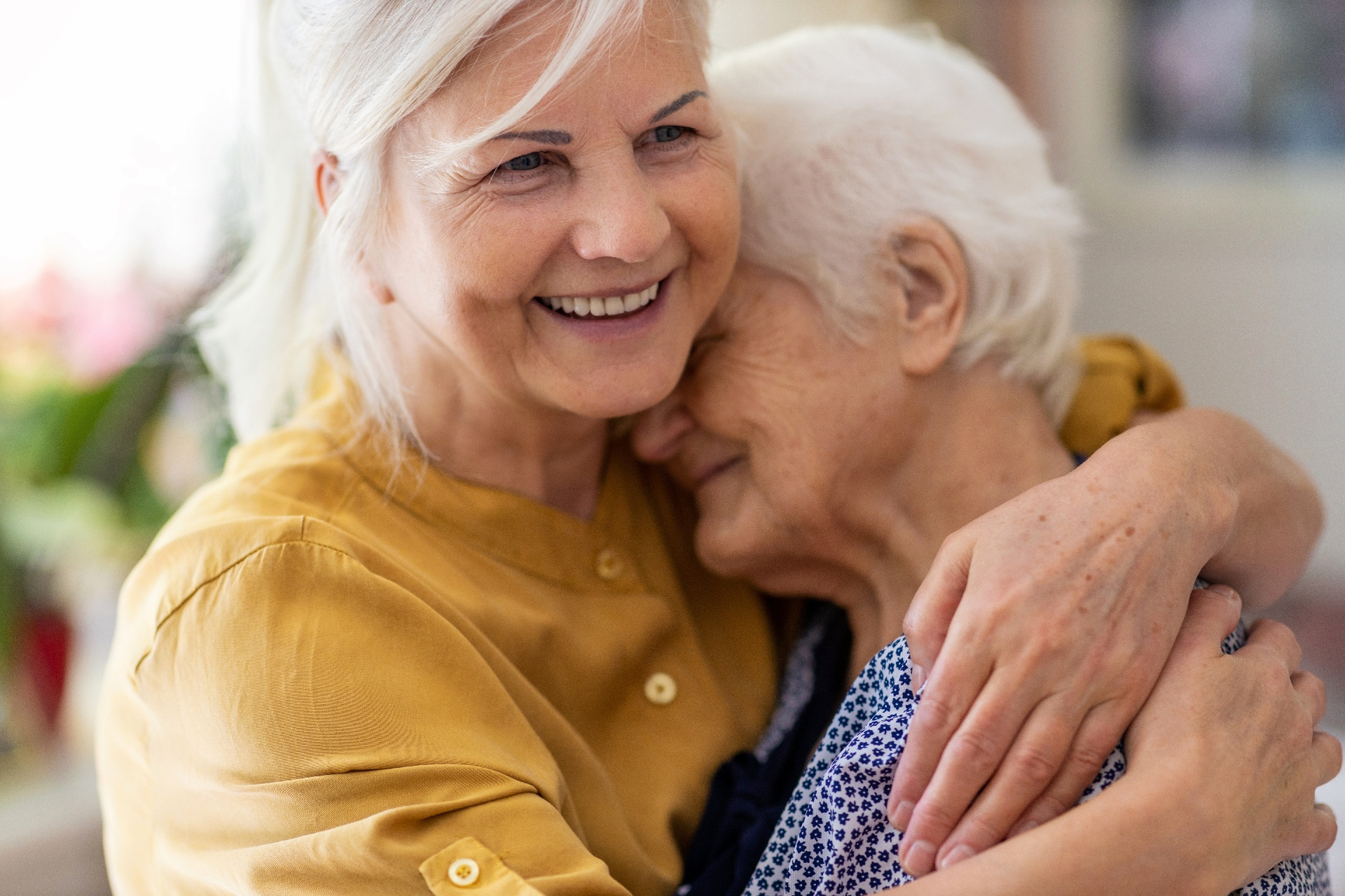 A mother and daughter hugging and smiling
