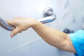 Senior grabbing hand rail in shower stall