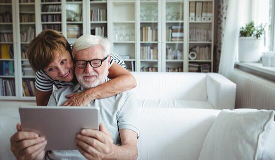 woman hugging man from behind couch who is looking at a tablet computer