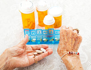 Senior placing pills into a container