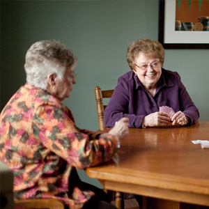 two elderly women playing cards